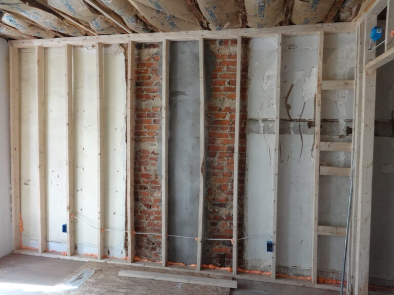 Interior wall framing against masonry wall