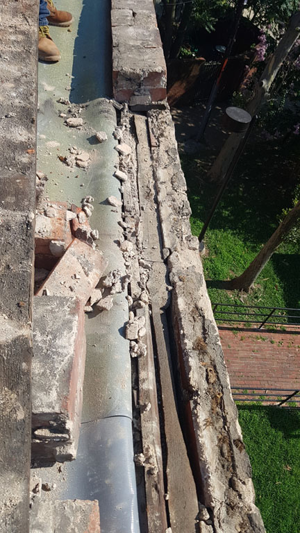 Brick parapet and underlying nailer board with roof membrane pulled back to expose substrate