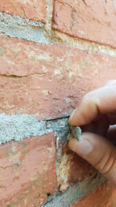 Scam pointing delamination - modern Portland smeared over deteriorated mortar joint -less than quarter inch depth